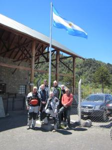 Our little group of riders, posing for a picture beneath the Argentine flag, at the border crossing.